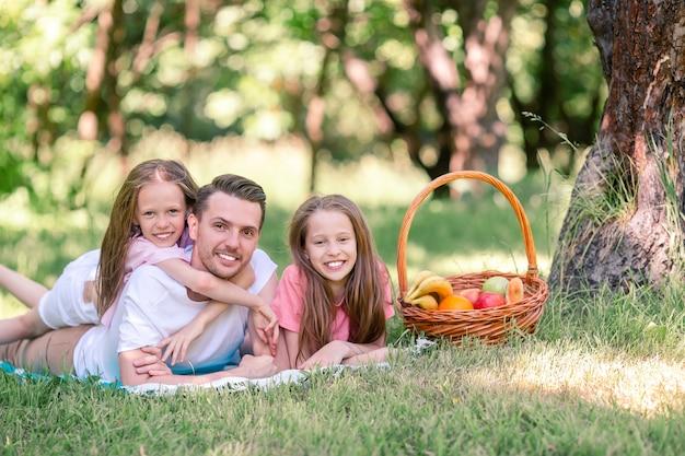 Heureux père et petites filles se détendre au bord du lac Photo Premium