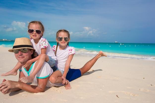 Heureux père et ses adorables petites filles sur une plage tropicale Photo Premium
