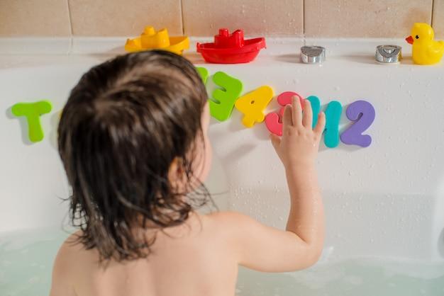Heureux petit bébé dans la salle de bain, jouant avec des lettres et des bulles de mousse. hygiène et soins pour les jeunes enfants. Photo Premium