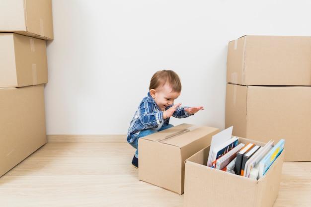 Heureux petit bébé garçon jouant avec des boîtes en carton à la nouvelle maison Photo gratuit