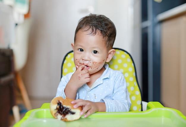 Heureux petit garçon asiatique assis sur une chaise pour enfants mangeant du pain avec du chocolat farci Photo Premium
