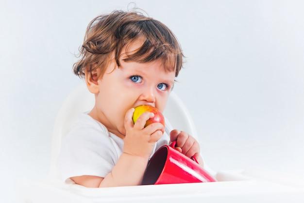Heureux Petit Garçon Assis Et Mangeant Photo gratuit