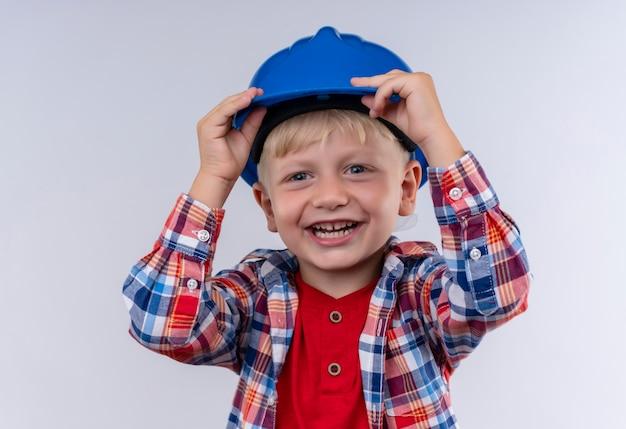 Un Heureux Petit Garçon Aux Cheveux Blonds Portant Chemise à Carreaux Tenant Son Casque Bleu Tout En Regardant Sur Un Mur Blanc Photo gratuit