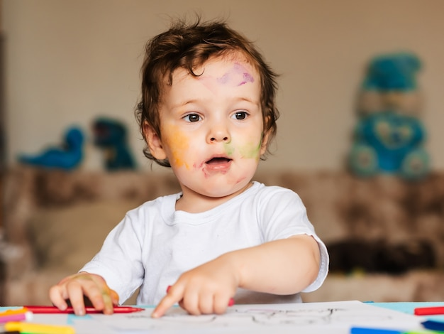 Heureux Petit Garçon Dessine Avec Des Crayons De Couleur Dans Un Album Photo Premium