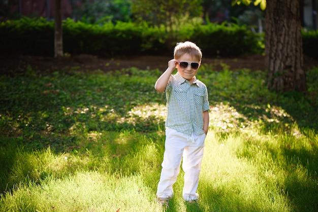 Heureux petit garçon avec des lunettes de soleil dans le jardin. Photo Premium