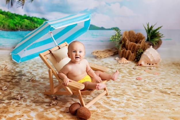 Heureux Petit Garçon, Se Trouve Sur Une Chaise Longue En Bois, Des Bains De Soleil Sur Une Plage De Sable Avec Des Palmiers Au Bord De La Mer Photo Premium