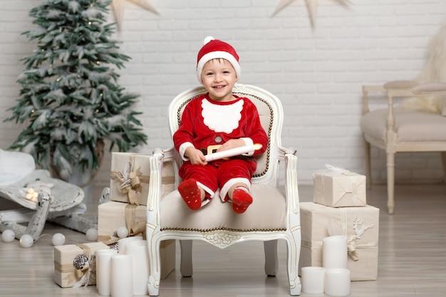 Heureux petit garçon souriant en costume de père noël est assis sur un fauteuil près de sapin de noël et détient une bougie blanche dans les mains Photo Premium