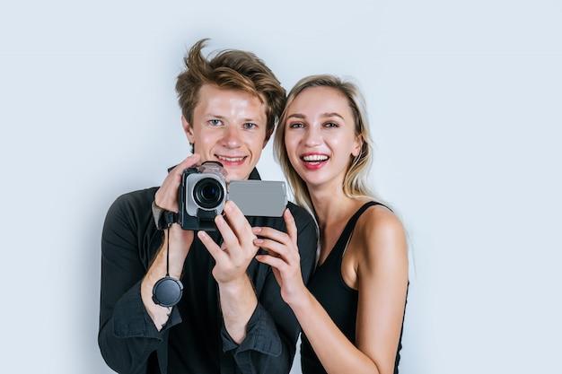 Heureux portrait d'un couple tenant une caméra vidéo et enregistrer un clip vidéo Photo gratuit