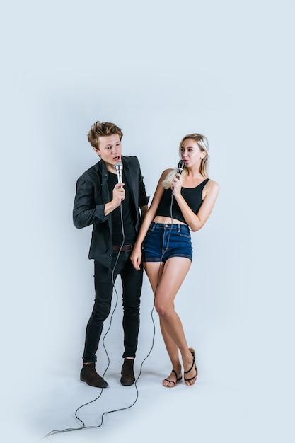 Heureux portrait d'un couple tenant un micro et chanter une chanson Photo gratuit