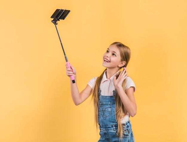 Heureux portrait d'une fille agitant sa main prenant selfie sur téléphone portable sur fond jaune Photo gratuit