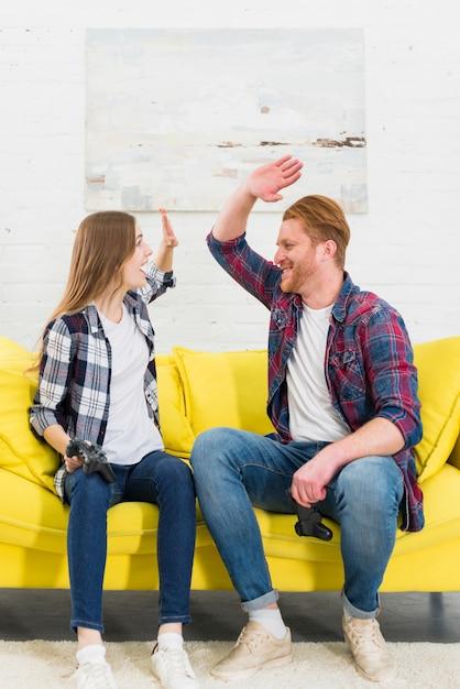 Heureux portrait de jeune couple faisant cinq gestes les uns après les autres après avoir joué à la console de jeu Photo gratuit