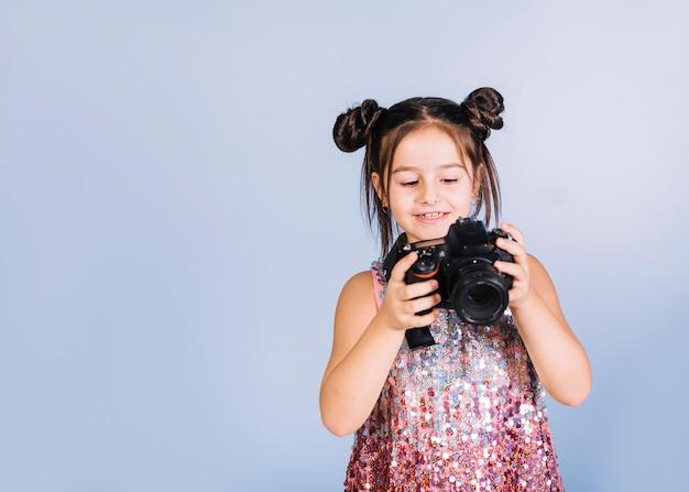Heureux portrait d'une jeune fille en regardant la caméra sur fond bleu Photo gratuit