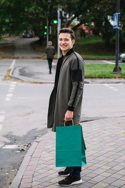 Heureux portrait de jeune homme souriant, debout sur le trottoir, tenant le sac shopping vert Photo gratuit
