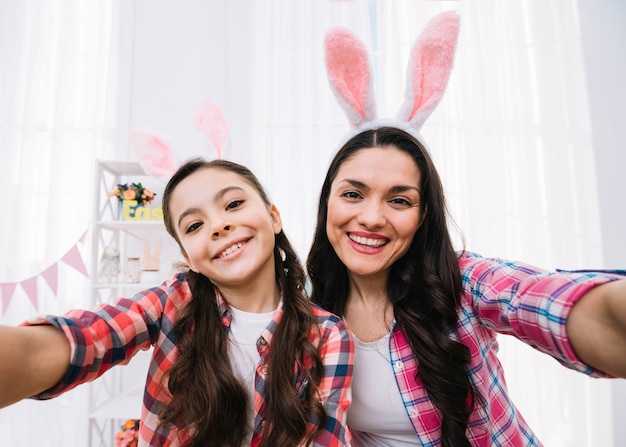 Heureux portrait de mère et fille prenant selfie le jour de pâques Photo gratuit