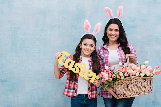 Heureux portrait de mère et fille tenant le panier de mots et de tulipes de pâques contre le mur bleu Photo gratuit