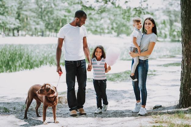 Heureux propriétaires d'animaux jeune famille marchant avec un chien Photo Premium
