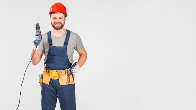 Heureux réparateur tenant perceuse à la main Photo gratuit