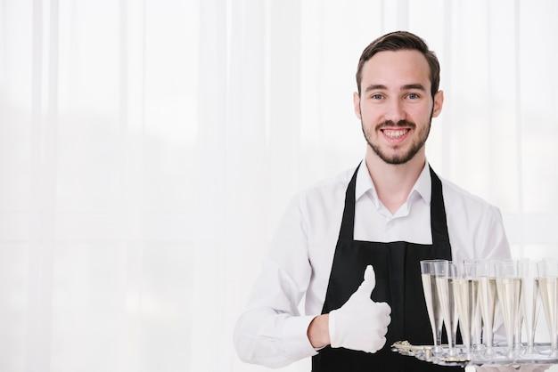 Heureux serviteur portant des coupes à champagne avec espace de copie Photo gratuit