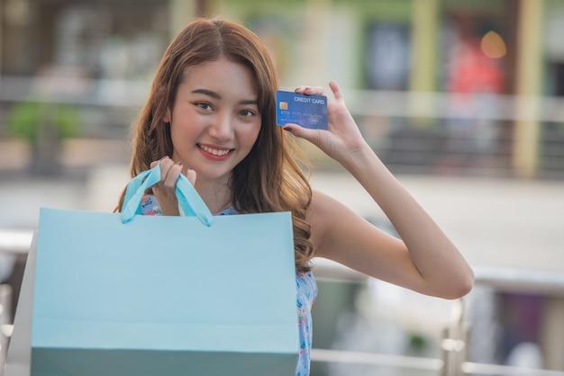 Heureux Shopping Concept De Temps, Jeune Femme Asiatique Avec Des Sacs à Provisions Et Détenant La Carte De Crédit En Main Au Centre Commercial. Photo Premium