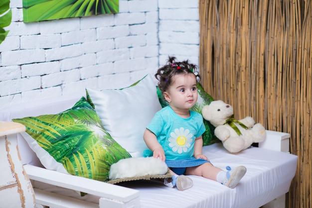 Heureux souriant bébé douce fille assise sur le canapé avec ourson Photo Premium