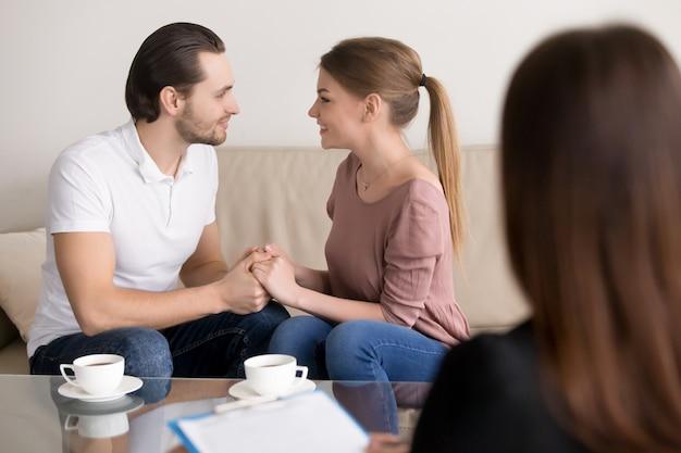 Heureux, sourire, jeune couple, tenant mains, consultation, psychologue, planification mariage Photo gratuit