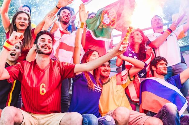 Heureux supporters au stade avec drapeaux et bombe fumigène Photo Premium