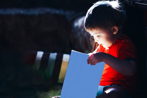 Heureux surpris garçon de trois ans en lisant un livre de conte de fées magique, la lumière vient de livre, livre isolé Photo Premium