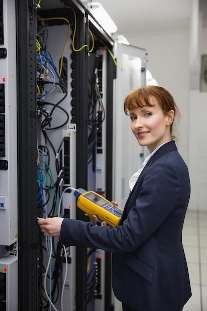Heureux technicien utilisant un analyseur de câble numérique sur serveur Photo Premium