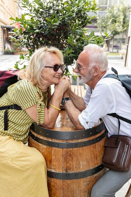 Heureux vieux couple main dans la main sur un tonneau Photo gratuit