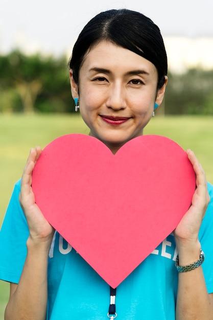 Heureux volontaire japonais avec un coeur Photo gratuit