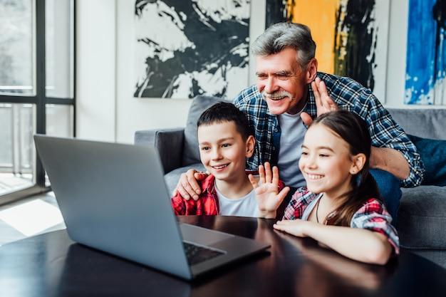 Héy. retraité à l'esprit positif et ses petits-enfants souriant et agitant la main tout en ayant un appel vidéo à la maison. Photo Premium