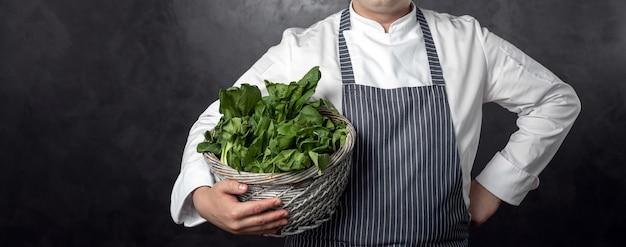 Hhand tient un panier avec une salade verte Photo Premium