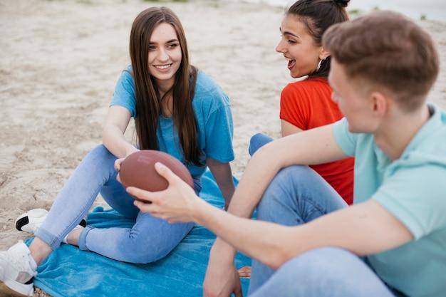 High angle amis heureux avec ballon de football Photo gratuit