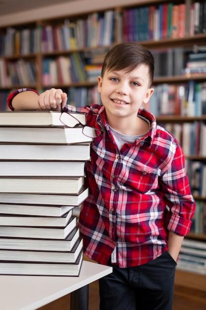High Angle Boy Avec Pile De Livres à La Bibliothèque Photo gratuit