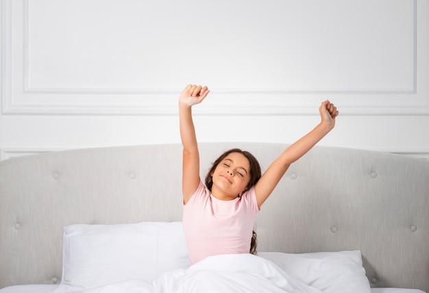 High angle girl sur le lit se réveiller Photo gratuit