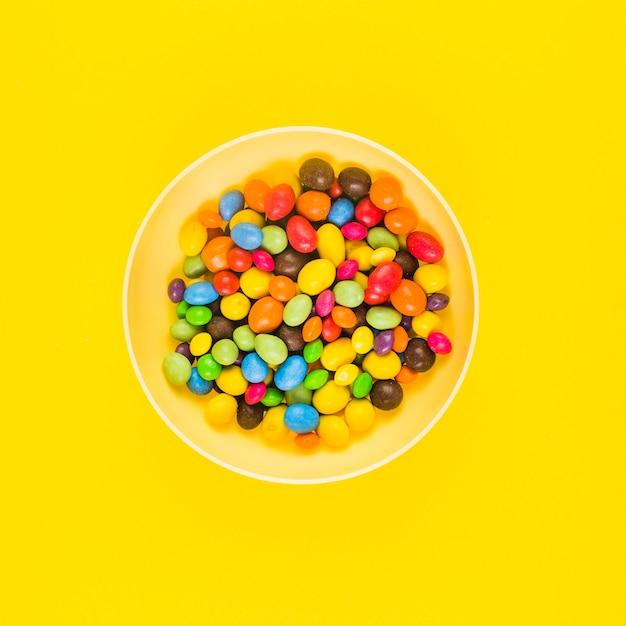 High angle de vue de bonbons colorés sur une plaque sur une surface jaune Photo gratuit