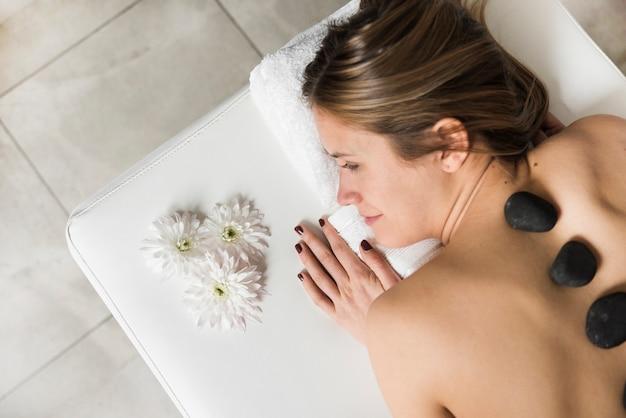 High Angle De Vue D'une Jeune Femme Allongée Sur Le Lit, Recevant Un Massage Aux Pierres Chaudes Photo gratuit