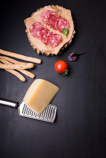 High Angle De Vue De Pepperoni Sur Un Dessous De Verre En Bois Avec Tomate; Des Bâtons De Pain; Fromage Et Râpe Photo gratuit