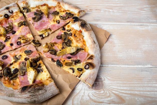 High angle de vue de pizza au pepperoni aux champignons en tranches sur du papier brun au-dessus d'une table en bois Photo gratuit