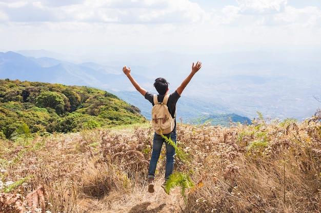 Hiker levant les bras vers le ciel Photo gratuit