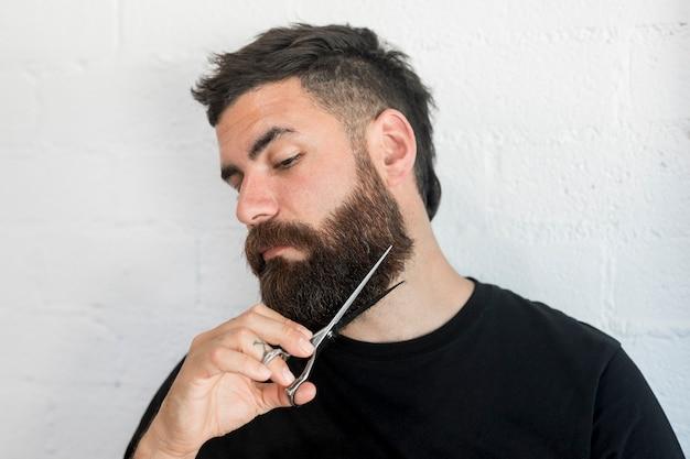 Hippie mâle coupant la barbe avec des ciseaux Photo gratuit