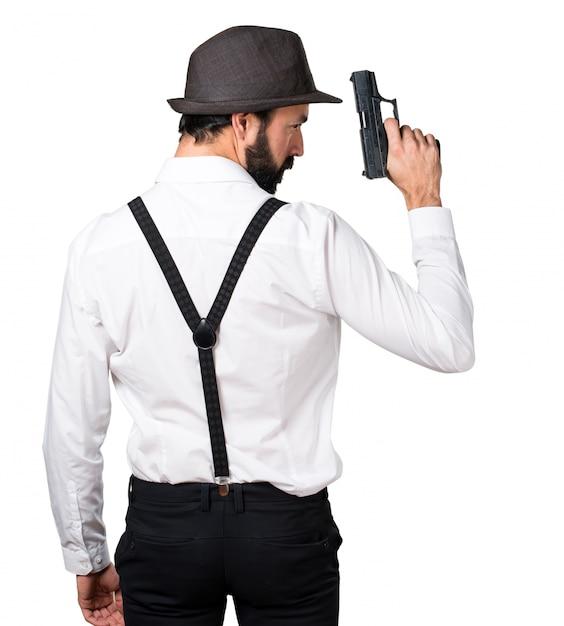 Hipster homme à la barbe avec un pistolet Photo gratuit