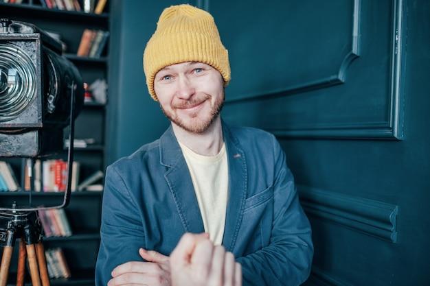 Hipster homme chauve attrayant souriant avec barbe au chapeau jaune montre poing geste indécent Photo Premium