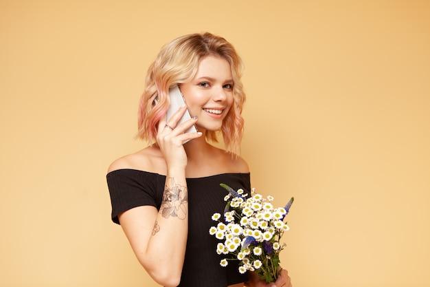 Hipster jeune femme avec des cheveux bouclés colorés et tatouage souriant et parlant au téléphone, tenant des fleurs Photo Premium