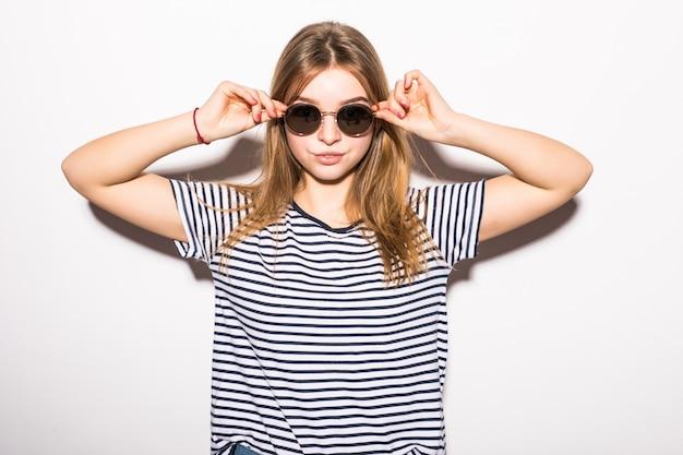 Hipster Mode Jeune Femme à Lunettes De Soleil Isolé Sur Mur Blanc Photo gratuit