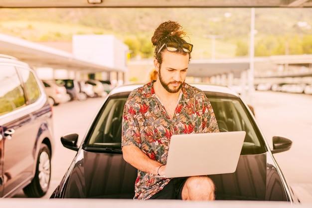 Hipster avec ordinateur portable assis sur le capot de la voiture Photo gratuit