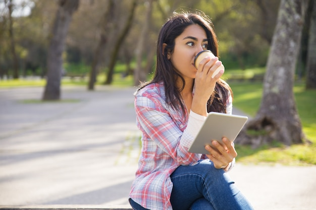 Hipster paisible fille appréciant ebook et café du matin dans le parc Photo gratuit