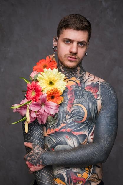 Hipster tatoué jeune homme avec une fleur sur son corps et perçant dans ses oreilles et son nez en regardant la caméra Photo gratuit