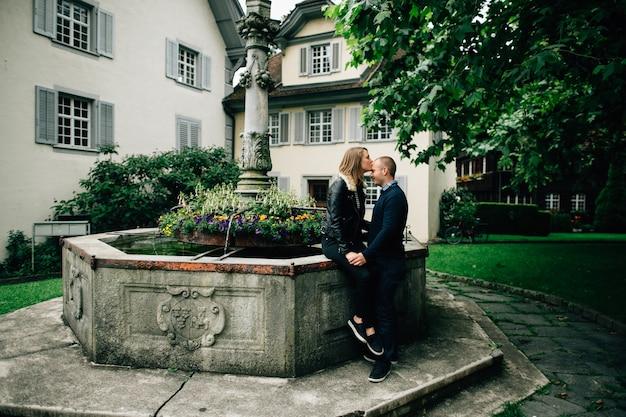 Histoire d'amour. jeune couple amoureux s'embrasser près de la belle fontaine avec des fleurs. Photo gratuit