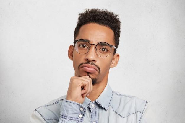 Hmm Pas Mal. Close Up Portrait En Studio De Gestionnaire Masculin Sérieux Concentré Ou Patron évalue Le Travail D'autres Personnes Photo gratuit
